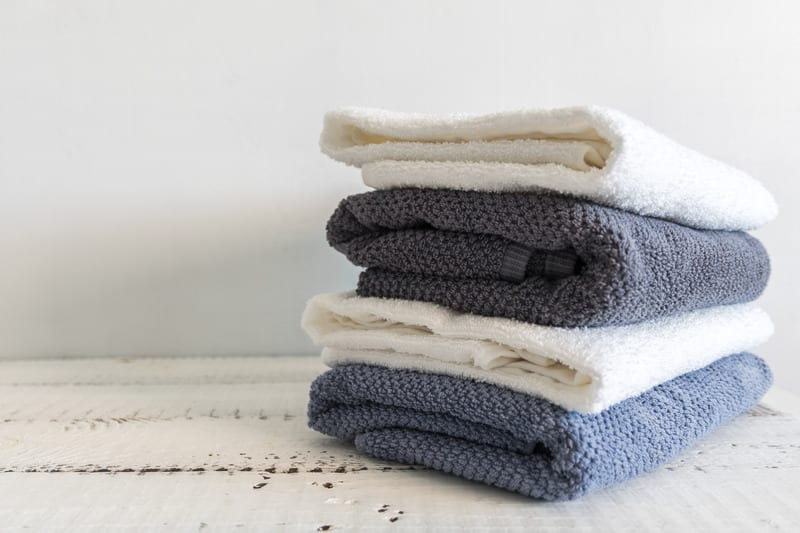 A stack of white and grey bath towels on white wooden table. Spa and wellness, cotton terry textile - Air Quality Express Pearland Dryer Vent Cleaning