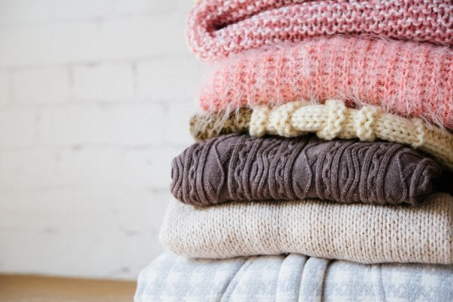 Pile of winter clothes made from Knitting on wooden surface, knitted sweaters and cardigans - Air Quality Express Katy Dryer Vent Cleaning