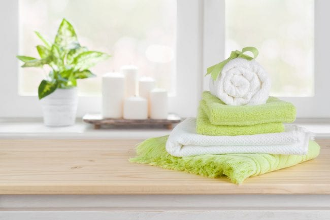 Spa towels on wooden table over blurred salon window background - Air Quality Express Dryer Vent Cleaning in Houston