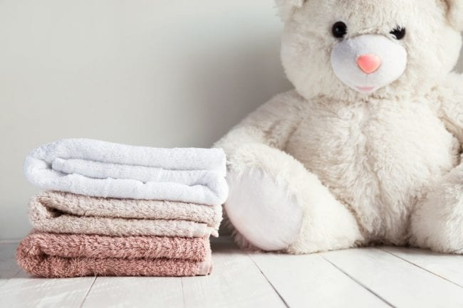 Stack of spa towels on white wooden table with white soft toy bear on background. Childrens washing concept - Air Quality Express Pasadena Dryer Vent Cleaning